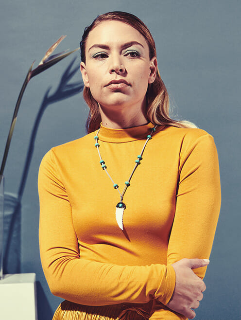 adjustable suede with white feather pendant on yellow shirt