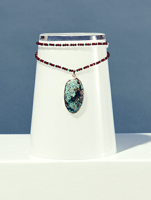 turquoise stone on maroon and blue crystal beads lifestyle