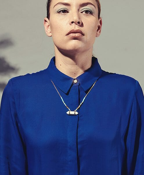 point pendant with turquoise beads on gold chain blue shirt